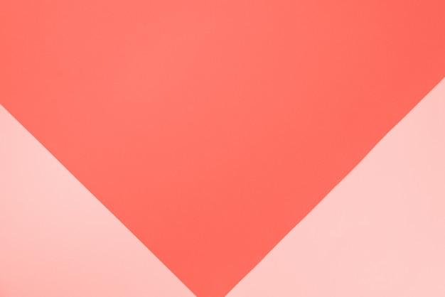 サンゴ色の背景。おしゃれなピンクとオレンジ紙。上面図。最小限のコンセプト。 Premium写真