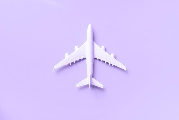白い飛行機、コピースペースでトレンディなバイオレット色の背景上の飛行機。 Premium写真