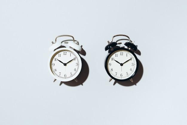 黒い目覚まし時計と灰色の背景にハードシャドウと白い目覚まし時計。 Premium写真