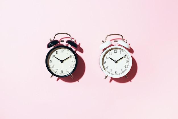 黒の目覚まし時計とピンクの背景のハードシャドウと白いもの。 Premium写真