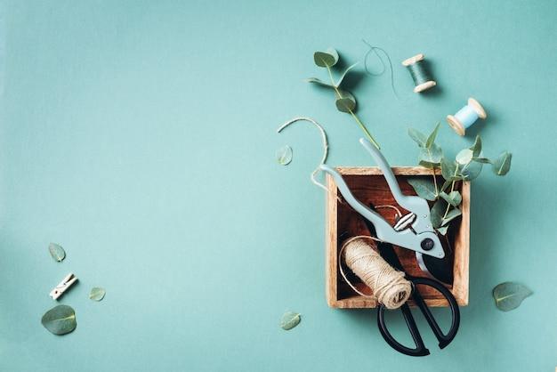 ユーカリの枝と葉、庭の剪定はさみ、木箱 Premium写真