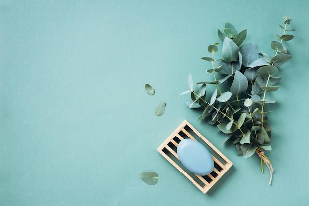 ユーカリのエッセンシャルオイルと緑の背景の石鹸。無駄のない、自然なオーガニックのバスルームツール。 Premium写真