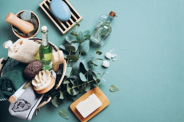 緑の背景にユーカリとマッサージとスパ製品。無駄のない、自然なオーガニックのバスルームツール。 Premium写真