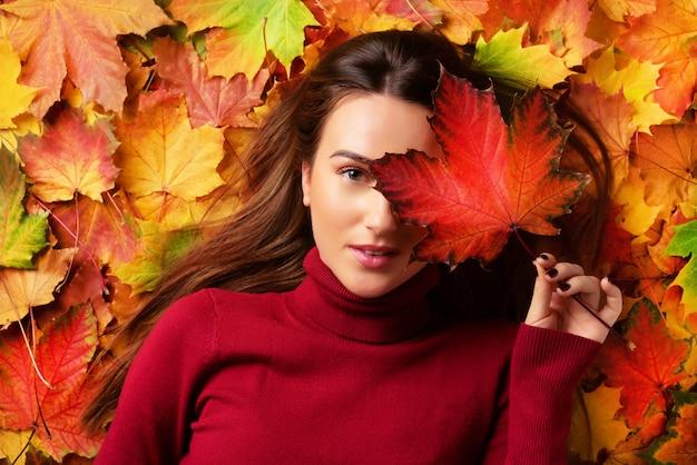 カラフルな落ち葉の背景に赤いカエデの葉を手で保持している女の子。ゴールドの居心地の良い秋のコンセプト。 Premium写真