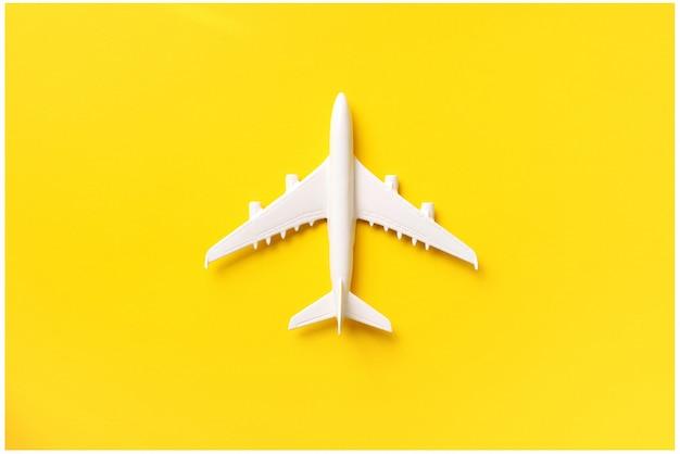 白い飛行機、コピースペースと黄色の背景に飛行機。 Premium写真