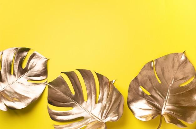 コピースペースと黄色の背景に黄金の熱帯モンステラリーフ。 Premium写真
