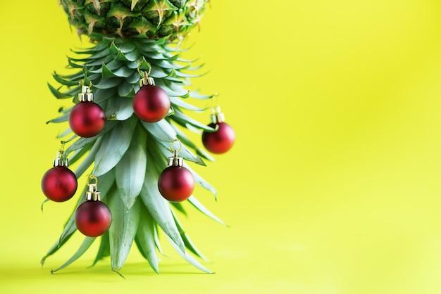 Творческая рождественская елка сделанная из ананаса и красной безделушки на желтой предпосылке, космосе экземпляра. Premium Фотографии