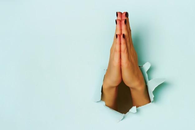 破れた青い紙の背景を通して若い女性の手を祈ってください。 Premium写真