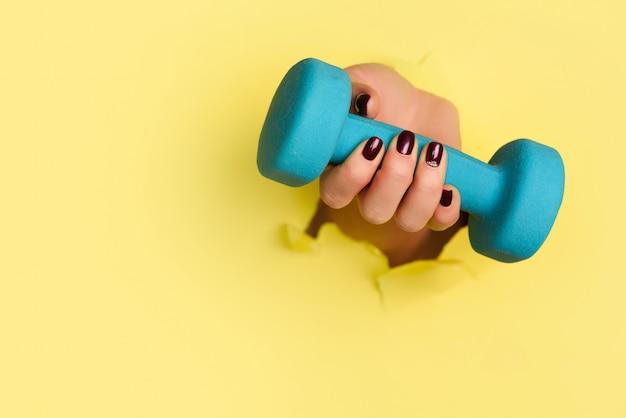 Рука женщины держа голубую гантель на желтой предпосылке. Premium Фотографии
