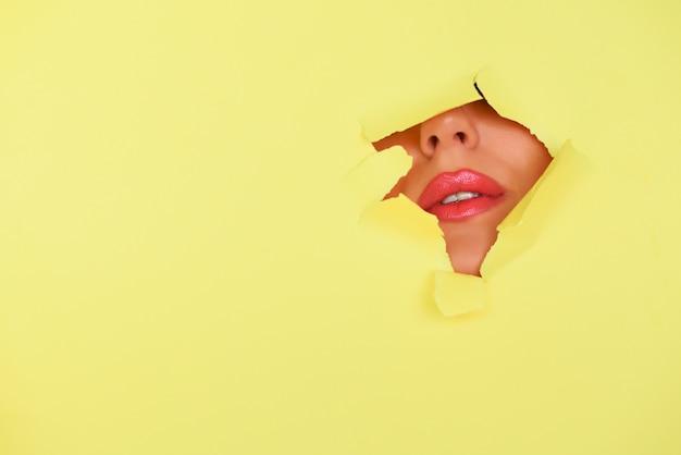 コピースペースを持つ美容室広告バナー。黄色い紙の背景の穴を通してキラキラと明るい唇のビュー。 Premium写真