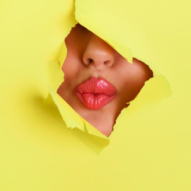 用紙の背景の穴を通してキスを与える美しいピンクの唇の眺め。 Premium写真