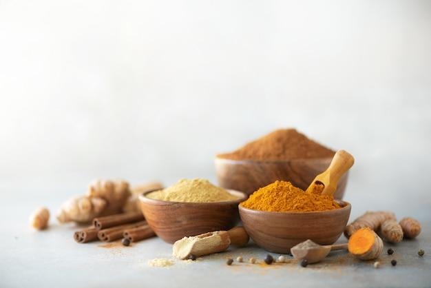 ウコンラテのための原料。灰色の背景に地上のウコン、ウコン根、シナモン、生姜、黒胡椒。 Premium写真