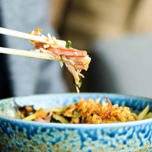 男の手が日本、タイ、中国の食事 - 米、きのこ、野菜のプレートの上にお箸を持っています。 Premium写真