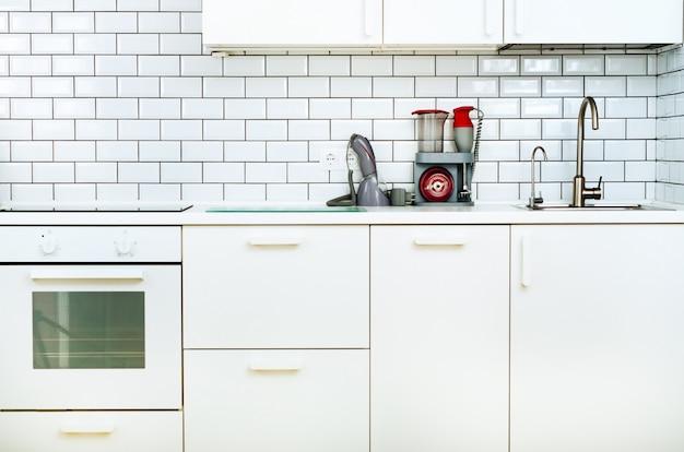 白のミニマルなキッチンインテリアとデザイン。タイル張りの壁 Premium写真