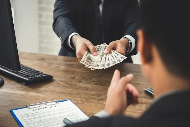 契約をしながら彼のパートナーにお金、日本円紙幣を与える実業家 Premium写真