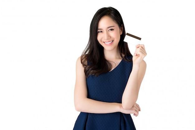 クレジットカードを手で提示する若い笑顔の美しいアジアの女性 Premium写真