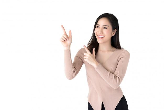 脇の空スペースに手を指している美しい若いアジア女性 Premium写真