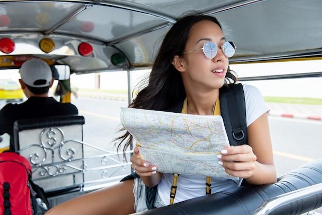 タイのバンコクのローカルトゥクトゥクタクシーで旅行する女性観光客 Premium写真