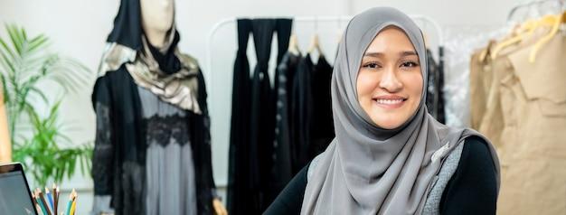彼女のテーラーショップでアジアのイスラム教徒の女性デザイナー Premium写真