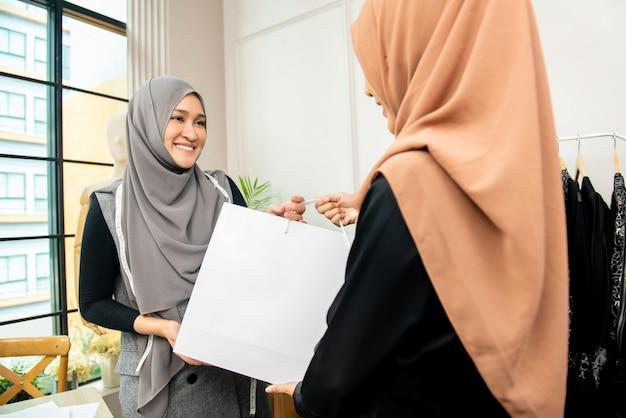 顧客に袋を与えるアジアのイスラム教徒の仕立て屋 Premium写真