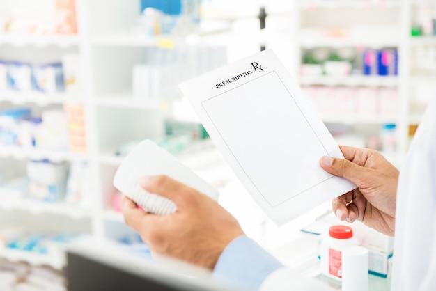 薬剤師が薬局で薬をチェック処方を保持 Premium写真