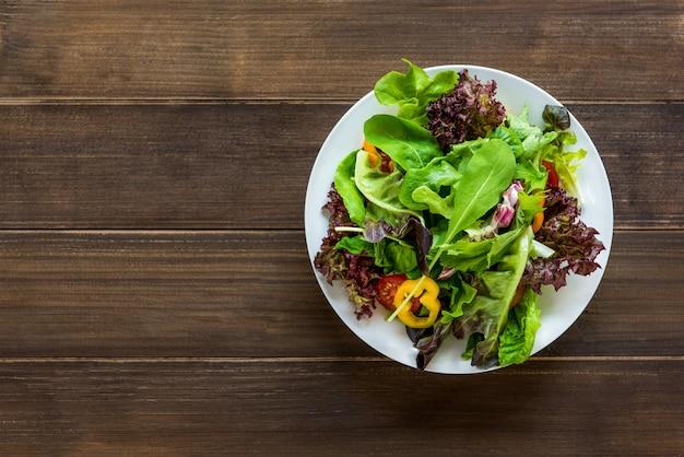 丸い白い皿にカラフルな健康的な新鮮なミックス野菜サラダ Premium写真