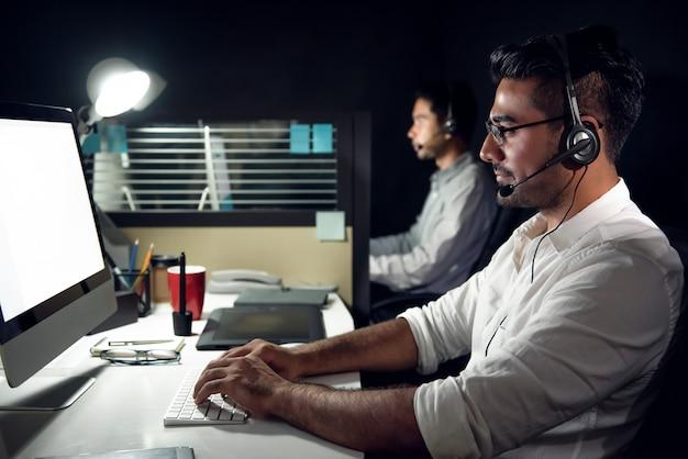 コールセンターで夜勤をしている男性のアジアカスタマーサービステレマーケティング Premium写真