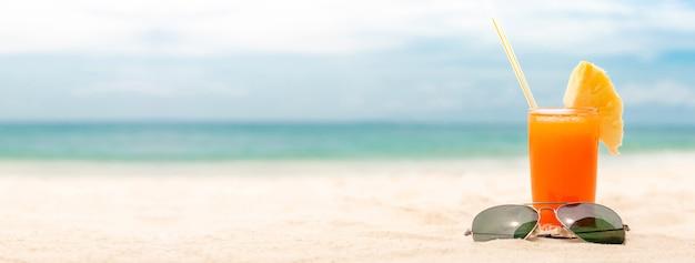 夏のビーチのバナーの背景にサングラスをかけたさわやかなトロピカルフルーツジュースを飲む Premium写真