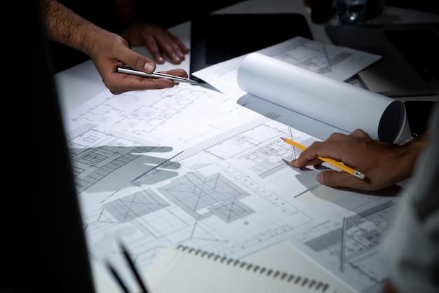 建築家チームのオフィスでの青写真紙を議論します。 Premium写真