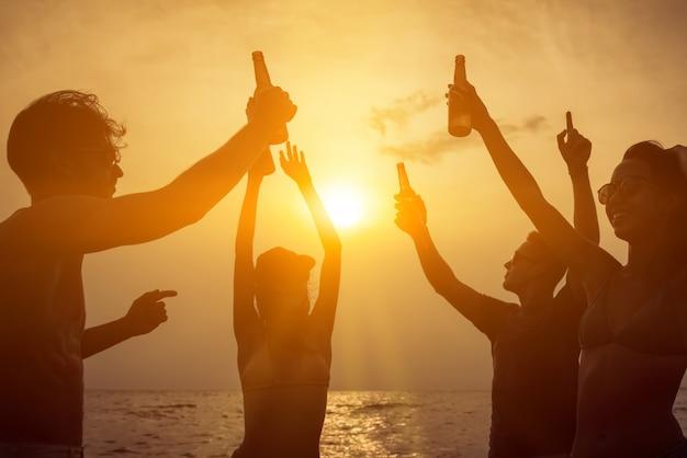Группа друзей, празднование и пить на пляже в сумерках закат Premium Фотографии
