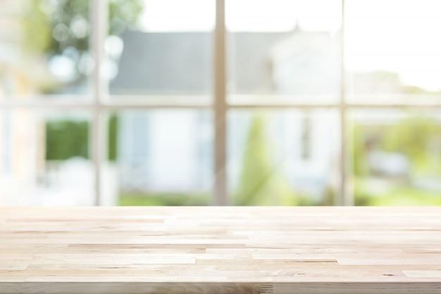 バックグラウンドでウィンドウと朝の日差しの木製テーブルトップ Premium写真