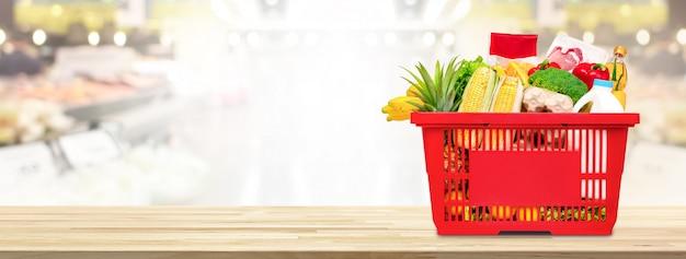 スーパーマーケットのテーブルの上に食べ物や食料品がいっぱい入った買い物かご Premium写真