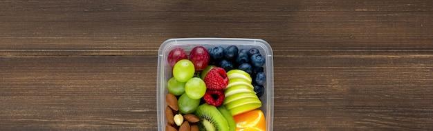 木製のバナーの背景にテイクアウトボックスにアーモンドと健康的な果物 Premium写真