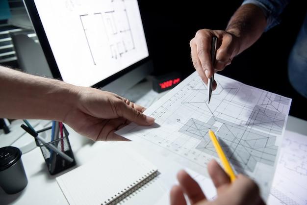 夜のオフィスでの青写真紙を議論する建築家チーム Premium写真