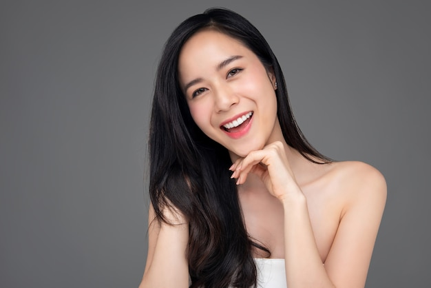 灰色の背景上の幸せな美しいアジアの女性の美しさの肖像画 Premium写真