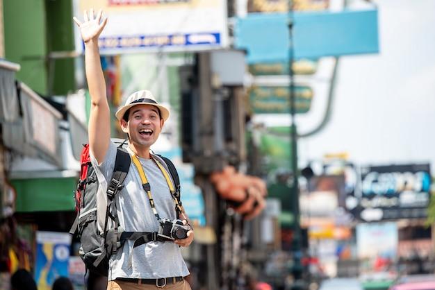 誰かに挨拶するために手を上げる興奮しているアジアの観光客男性 Premium写真