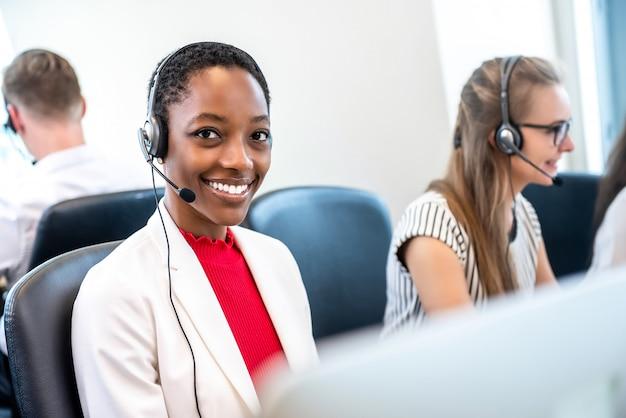 多様なチームとコールセンターのオフィスで働くアフリカ系アメリカ人女性 Premium写真