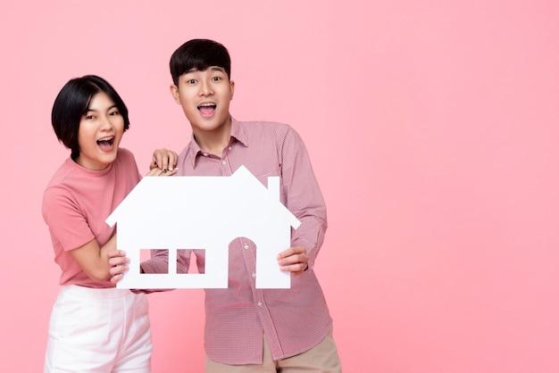 Молодая счастливая взволнованная азиатская пара, держащая бумажный дом Premium Фотографии