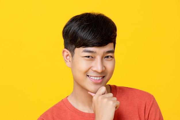 Красивый молодой азиатский человек усмехаясь с рукой на подбородке Premium Фотографии