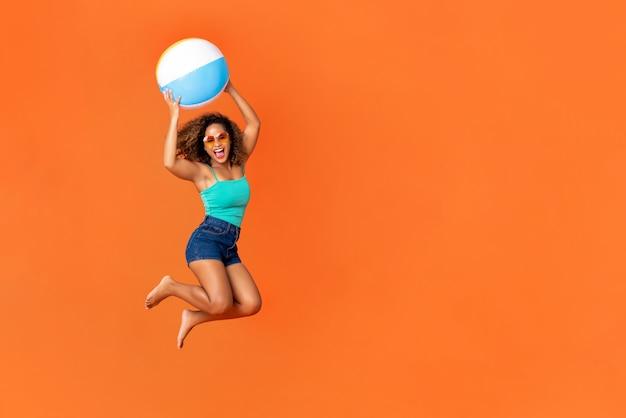 ビーチボールを押しながらジャンプのエネルギッシュな若いアフリカ系アメリカ人女性 Premium写真