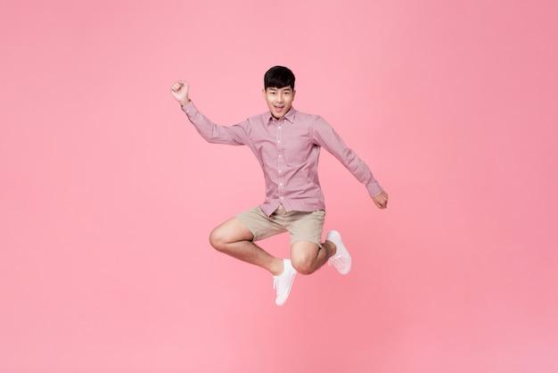 ジャンプのカジュアルな服装でエネルギッシュな笑顔若いアジア人 Premium写真
