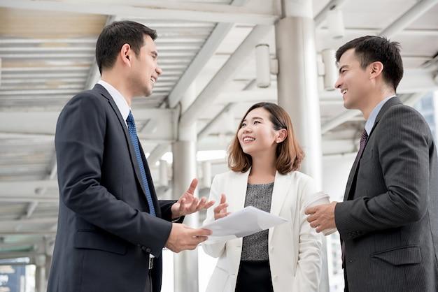 Счастливая азиатская деловая встреча за пределами офиса обсуждает работу Premium Фотографии