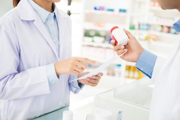 Аптекари показывая бутылку медицины и обсуждая отпускаемое по рецепту лекарство в аптеке. Premium Фотографии