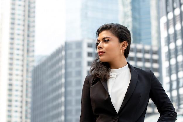 屋外に立っているフォーマルな服装の女性実業家 Premium写真