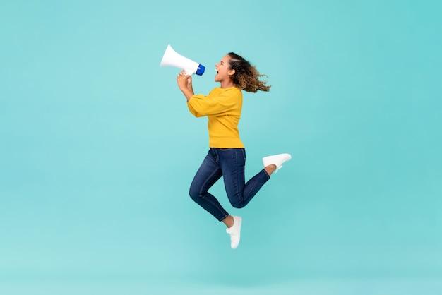 Девушка с мегафоном прыгает и кричит Premium Фотографии