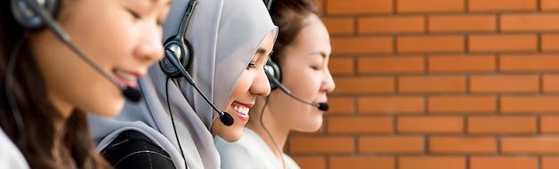 Красивая азиатская мусульманская женщина работая в центре телефонного обслуживания с ее командой Premium Фотографии