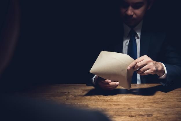 暗い部屋で彼のパートナーによって与えられた封筒をチェックする実業家 Premium写真
