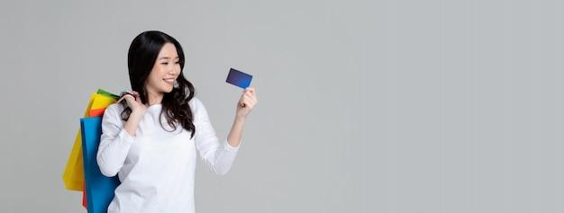 Счастливая азиатская женщина в белой футболке с длинным рукавом показывая кредитную карточку и нося изолированные хозяйственные сумки Premium Фотографии