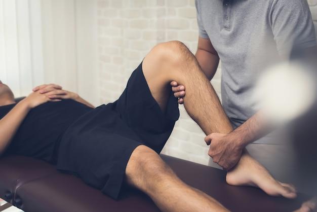 Физиотерапевт лечит спортсмена мужского пола пациента Premium Фотографии