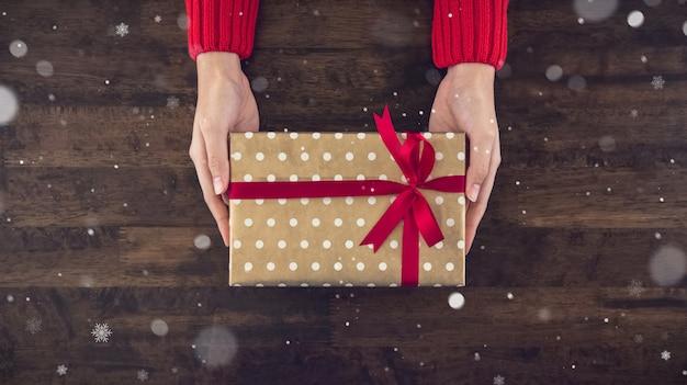 木製のテーブルにクリスマスギフトボックストップビューを与える女性の手 Premium写真
